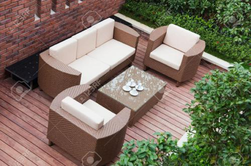 9228560-Home-exterior-patio-with-wooden-decking-and-rattan-sofa-view-from-the-top--Stock-Photo
